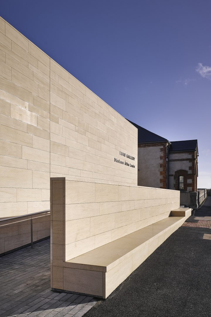 Detail of the stone facade, entrance ramp and bench on the new wing at the Luan Gallery