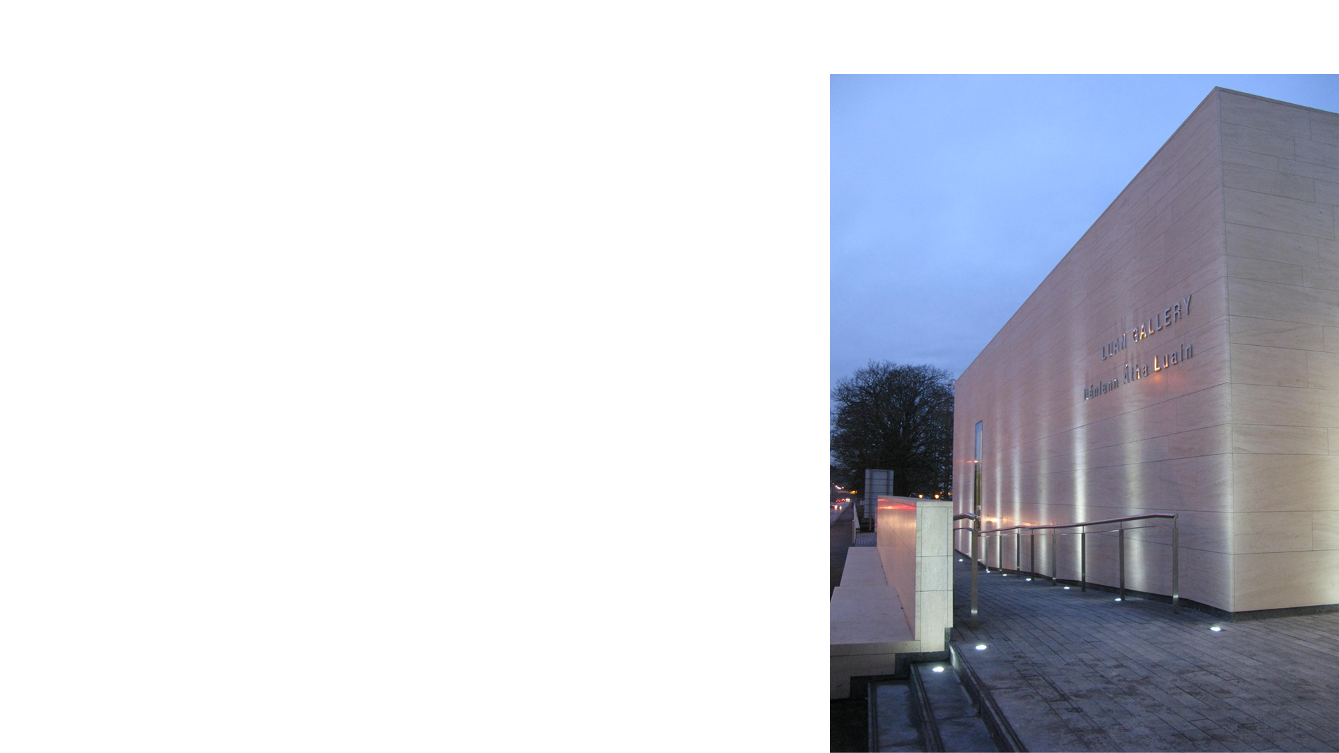 Detail of the stone facade and entrance ramp at dusk on the new wing at the Luan Gallery