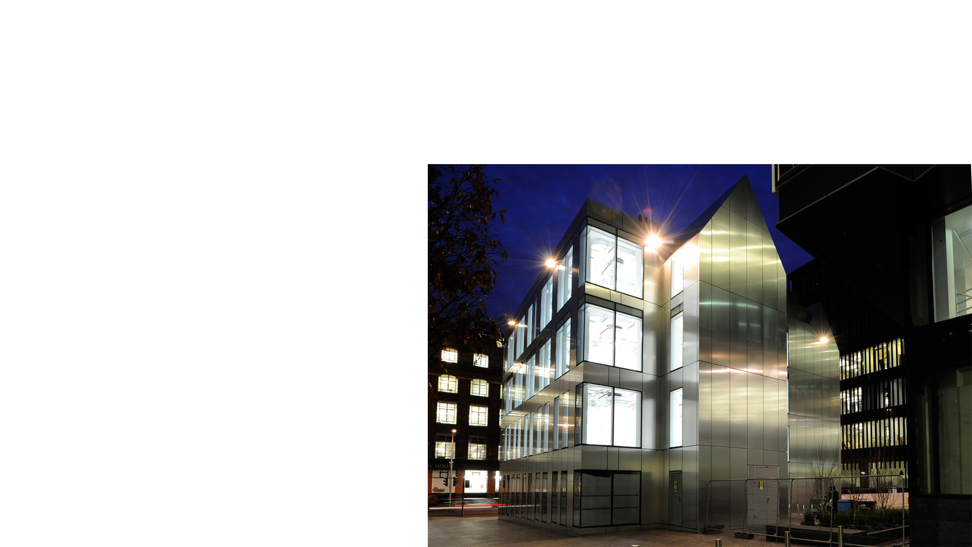 Nighttime image of stainless steel cladding to restored and remodelled former Tooley Street Fire Station