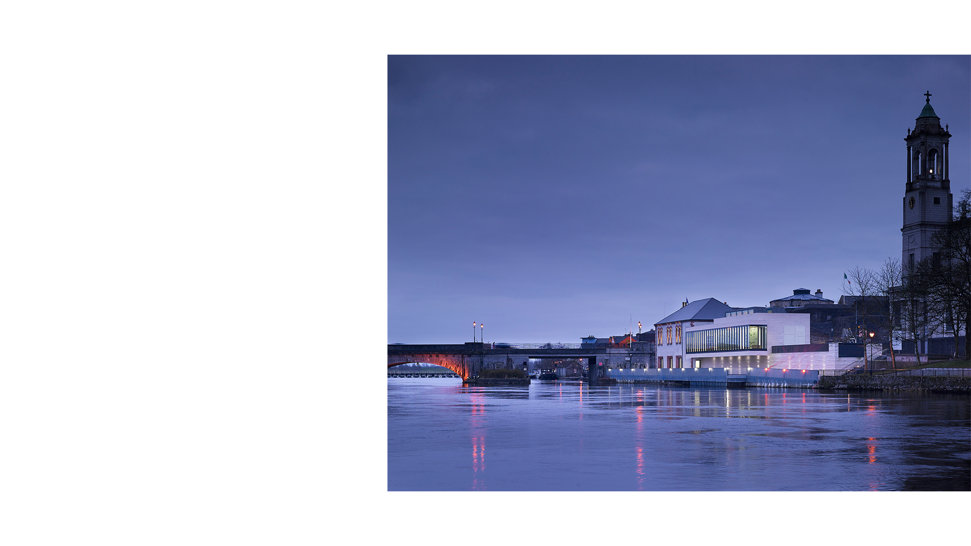 The Luan Gallery viewed upstream at dusk across the River Shannon. The tower of the church of St Peter and St Paul is silhouetted in the background